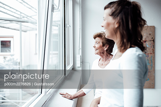 Happy grandmother with granddaughter looking through window at home - p300m2276826 by Gustafsson