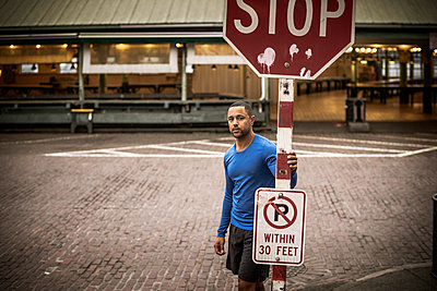 Portrait of athlete standing by stop sign on street - p1166m1096186f by Cavan Images