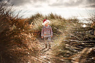 Toddler boy wearing Santa hat walking in sand dunes in the morning - p1166m2095096 by Cavan Images