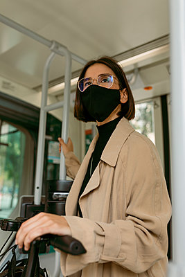 Mid adult woman wearing face mask standing with push scooter in tram - p300m2226777 by Valentina Barreto