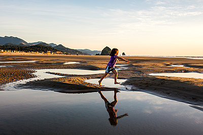 Caucasian girl running in tide pools on beach, Cannon Beach, Oregon, United States - p555m1413213 by Adam Hester