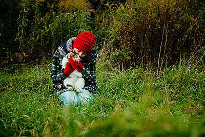 Teen Girl Kissing Her Cat on A Cold Fall Day in Michigan - p1166m2153344 by Cavan Images