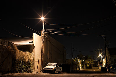 Wheelclamped Pick Up Truck Parked Under Streetlight At Night In Eerie Looking Back Alley - p1291m1548106 by Marcus Bastel