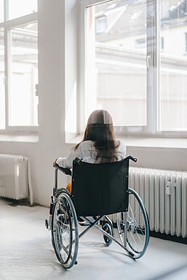 Young handicapped woman sitting in wheelchair, rear view - p300m2004109 by Kniel Synnatzschke