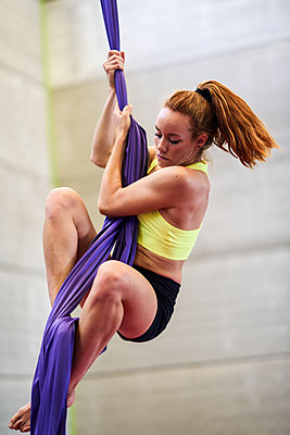 Young woman doing aerial silk in an exercise room - p300m2140671 by Javier Sánchez Mingorance