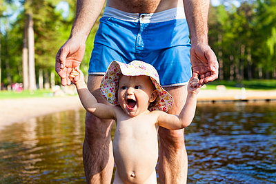 Father holding toddler at water - p312m2079320 by Anne Dillner