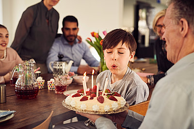 Boy blowing candles on birthday cake while enjoying in party with family at home - p426m1580210 by Maskot
