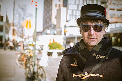 Caucasian man in top hat standing on city sidewalk - p555m1408626 by Alberto Guglielmi