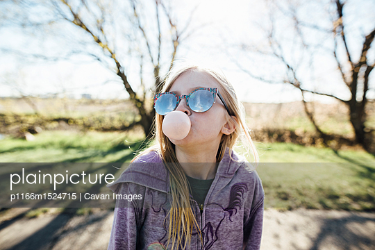 Girl wearing sunglasses blowing bubble gum while standing on road against sky - p1166m1524715 by Cavan Images
