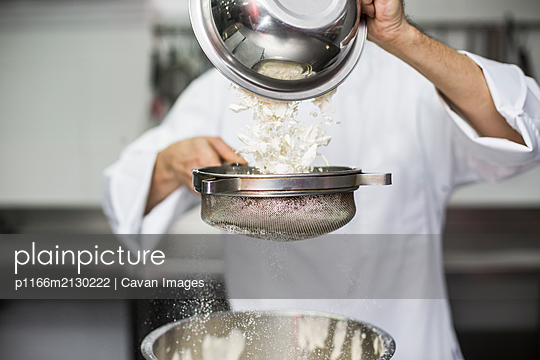 Chef sifting flour into bowl - p1166m2130222 by Cavan Images