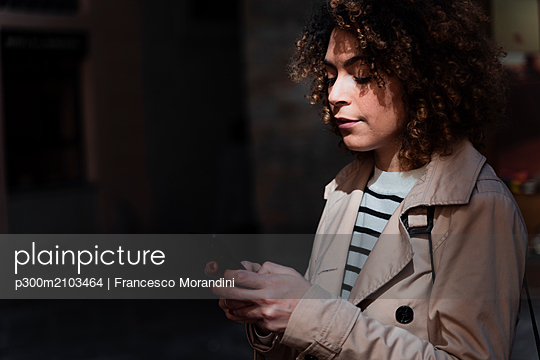 Woman using cell phone in an alley - p300m2103464 by Francesco Morandini