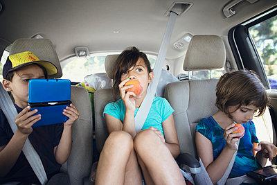 Siblings traveling in car - p1166m1174433 by Cavan Images