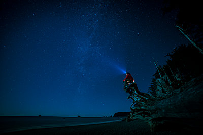 Hiker wearing headlamp sitting on tree trunk at La Push beach against sky at night - p1166m1485234 by Cavan Images