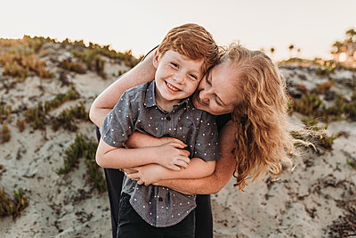 Front view of mother hugging redheaded kindergarten age son at sunset - p1166m2136561 by Cavan Images