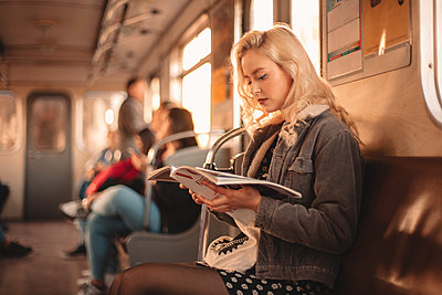 Young woman reading magazine while traveling in subway train - p1166m2153474 by Cavan Images
