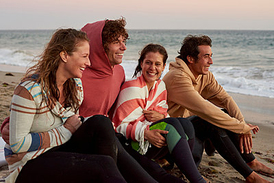 Happy friends sitting on the beach in the evening - p300m1206102 by Fotoagentur