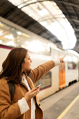 Young woman with cell phone at the train station pointing her finger - p300m2160322 by Valentina Barreto
