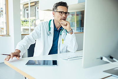 Male doctor with hand on chin using computer at office - p300m2293871 by Uwe Umstätter