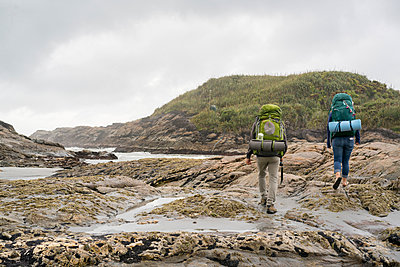 Young couple trekking over tide pools, rear view, Constant Bay, Charleston, South Island, New Zealand - p924m1197146 by Raphye Alexius
