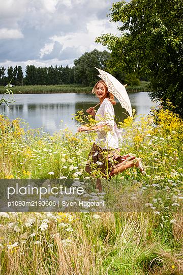 Blonde Frau läuft durch eine blühende Wiese - p1093m2193606 von Sven Hagolani