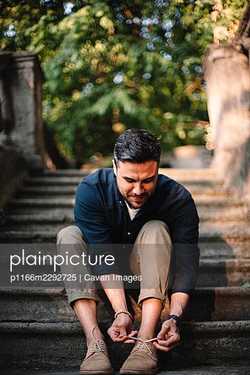 Happy man tying shoelace sitting on steps in city in summer - p1166m2292725 by Cavan Images