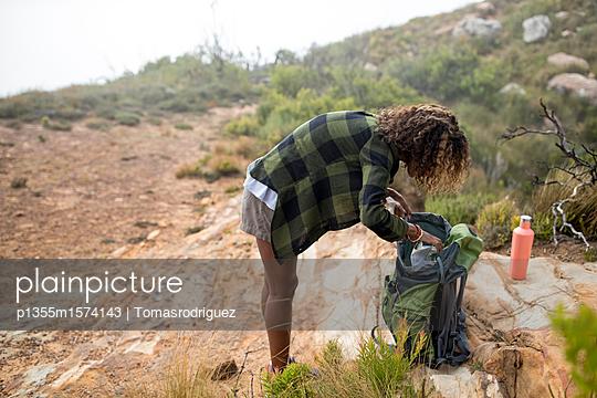 Junge Frau macht eine Pause auf ihrer Bergtour - p1355m1574143 von Tomasrodriguez