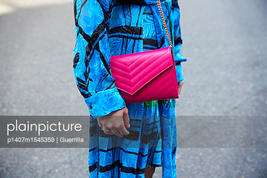 Mid section of a woman in blue dress with pink leather bag - p1407m1545359 by Guerrilla