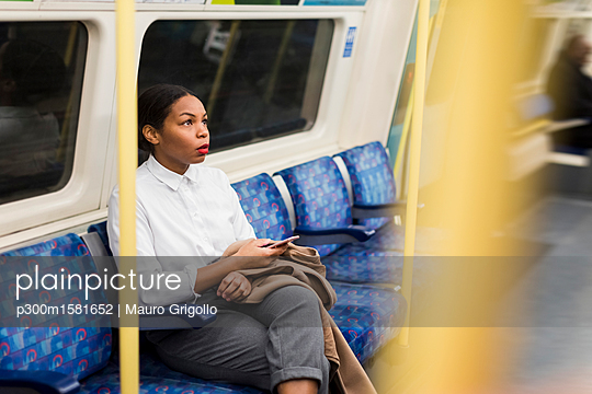 UK, London, businesswoman with cell phone sitting in underground train - p300m1581652 von Mauro Grigollo