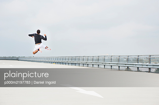 Young man jumping on a parking deck - p300m2197783 by Daniel Ingold
