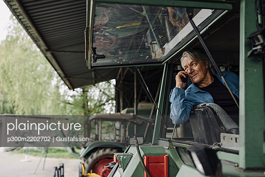 Senior man on the phone on a tractor on a farm - p300m2202702 by Gustafsson