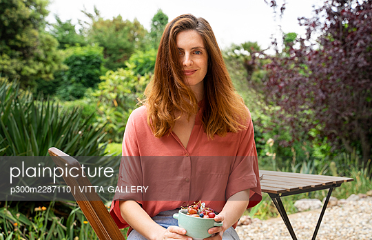 Woman with brown hair holding fruit bowl while sitting on chair in garden - p300m2287110 by VITTA GALLERY