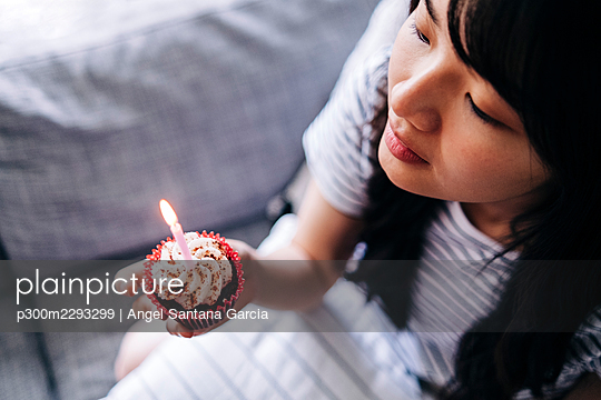 Young woman holding cupcake and candle while sitting on sofa - p300m2293299 by Angel Santana Garcia