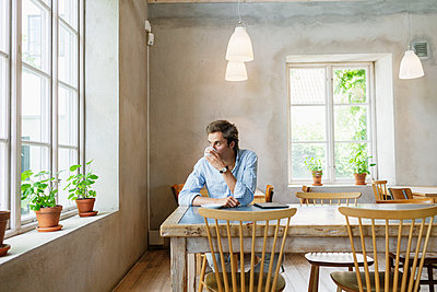 Man drinking coffee while looking through window at restaurant - p1264m1066924f by Astrakan