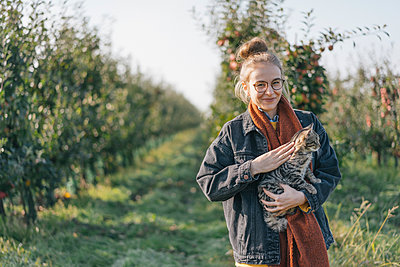 Young woman holding a cat in apple orchard - p300m1206237 by Kniel Synnatzschke