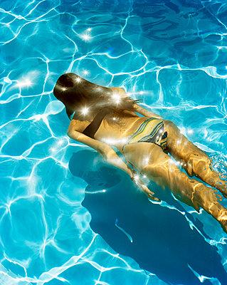 A Scandinavian woman swimming in a pool. - p312m1076764f by Nicho Sodling