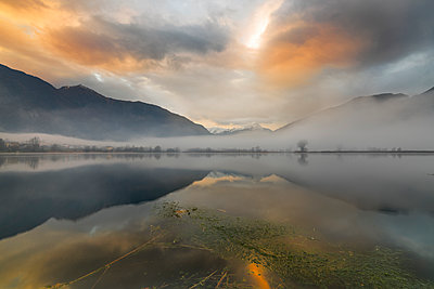 Mountains reflected in water at dawn shrouded by mist, Pozzo di Riva Novate, Mezzola, Chiavenna Valley, Lombardy, Italy, Europe - p871m1498214 by Roberto Moiola