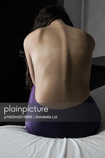 Junges Mädchen in lila Strumpfhose auf ihrem Bett - p1623m2215899 von Donatella Loi