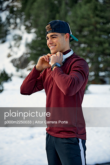 Smiling male sportsperson holding headphones while looking away during winter - p300m2250033 by Aitor Carrera Porté