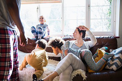 Multi-ethnic young family in pajamas playing in sunny living room - p1023m2016609 by Sam Edwards