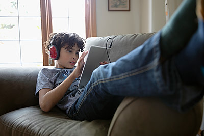 Latinx boy with headphones using digital tablet on sofa - p1192m2034510 by Hero Images