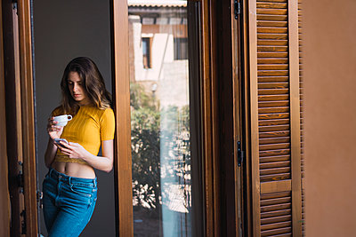 Young woman with coffee cup leaning against door case looking at cell phone - p300m1581066 von Kike Arnaiz