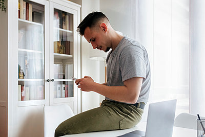 Handsome man using smart phone while sitting on desk at home office - p300m2266929 by Marco Govel