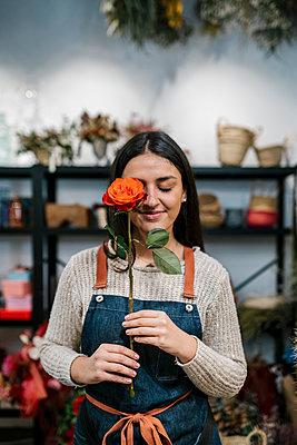 Smiling female florist covering eye with rose at shop - p300m2274945 by Ezequiel Giménez