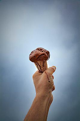 Mann hält tropfendes Schokoladeneis in der Hand - p397m1588945 von Peter Glass