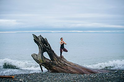 Mature woman practicing yoga tree pose on large driftwood tree trunk at beach - p924m1054092f by Pete Saloutos