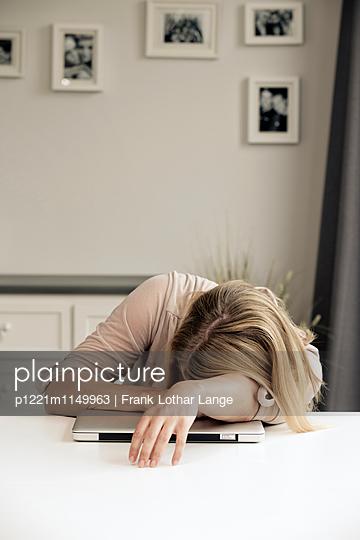 Erschöpfte Frau mit ihrem Laptop - p1221m1149963 von Frank Lothar Lange