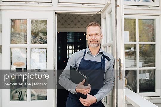 Portrait of restaurant owner standing by door - p426m2149154 by Maskot