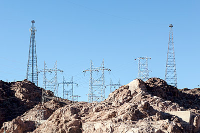 Low angle view of electricity pylons on rock formation against clear blue sky - p1094m1209099 by Patrick Strattner