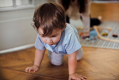 Cute baby boy crawling on Harwood floor with mother in background - p1166m1486007 by Cavan Images