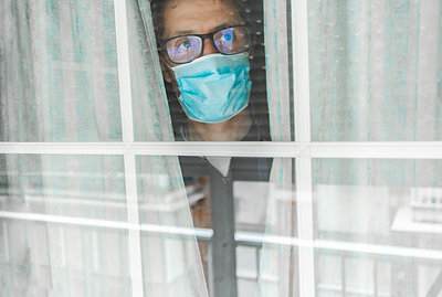 Middle-aged man in the medical mask is quarantined in the hospital and pressed her forehead against the window - p1166m2189818 by Cavan Images